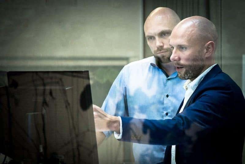 tø mænd der kigger på en skærm