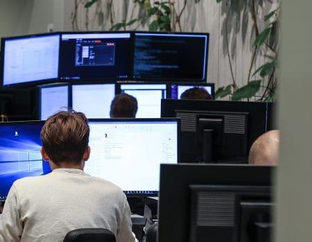 Udvikler kigger på mange skærme med data