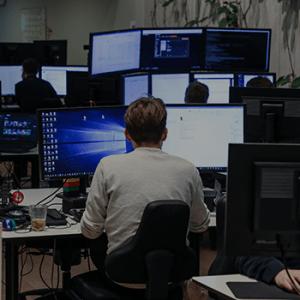 udvikler sidder og arbejder på mange skærme